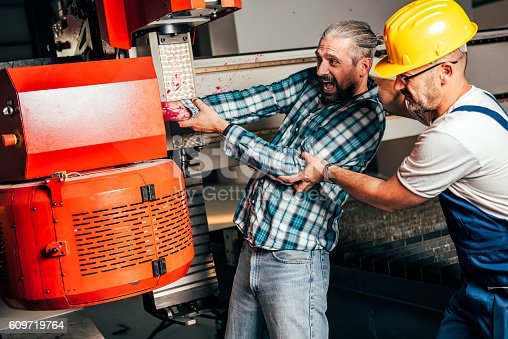 istock Worker caught in the machine and seriously injured 609719764
