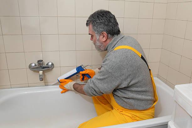 arbeiter abdichten badewanne und fliesen - fugen reinigen stock-fotos und bilder