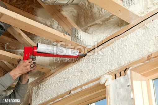 A construction worker is applying butyl sealant caulk to a gap between two window header boards at a house construction site. This is an optional measure to increase energy efficiency. The wall cavities have been sprayed with expandable foam insulation. In this home all of the board joints will be sealed with this caulk.
