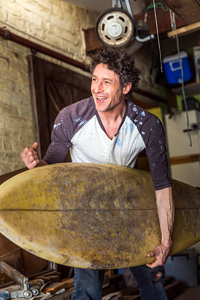 worker celebrating success while lifting surfboard in workshop - surf garage bildbanksfoton och bilder