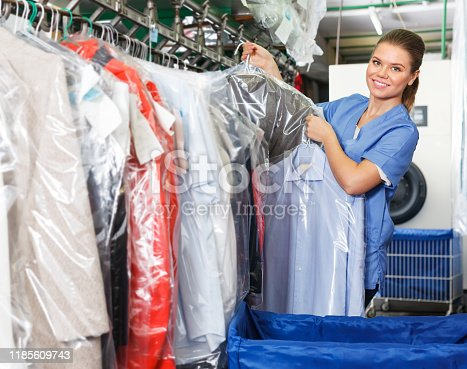 Woman working in modern dry cleaner, checking clean clothes hanging on rack