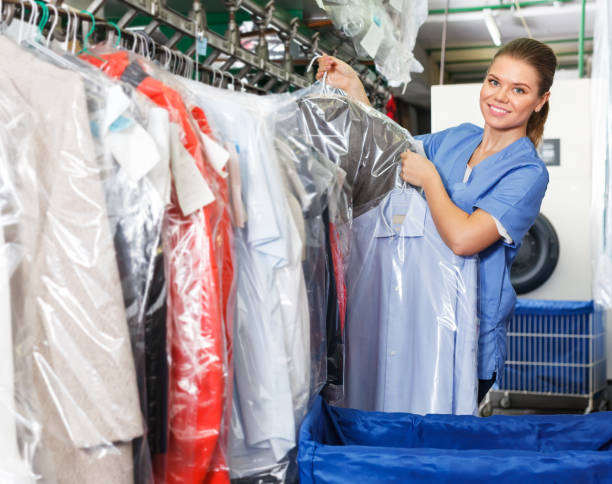 Worker checking clean clothes in laundry+ stock photo