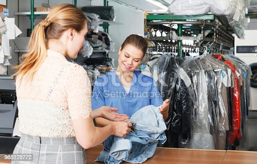 istock Worker checking clothes in dry cleaner 985125772