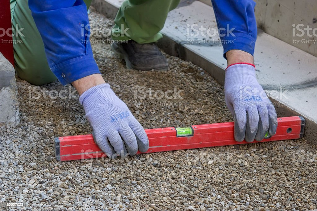 Worker checking horizontal level of ground for paving stock photo
