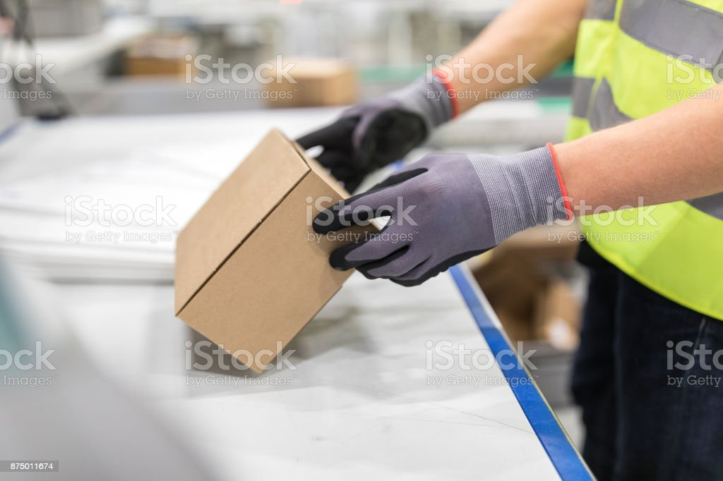 Worker checking package from conveyor belt in warehouse stock photo