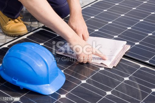 904490858istockphoto Worker checking plans on a solar photovoltaic panel 122197389