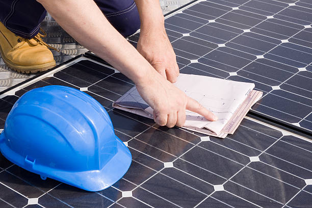 Worker checking plans on a solar photovoltaic panel stock photo