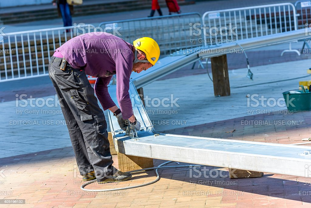 worker checking the fasteners on a metal beam stock photo