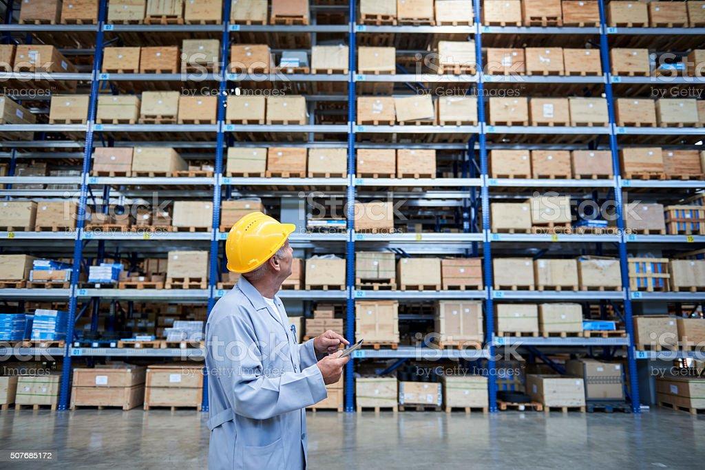 Empleado revisando los almacenes en el almacén - foto de stock