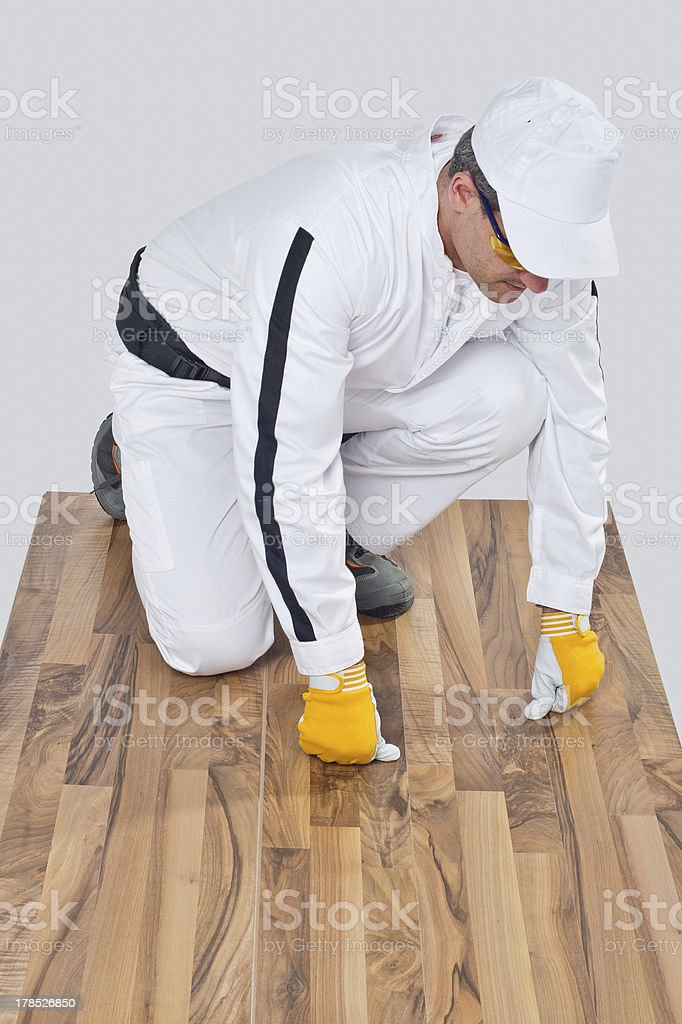 worker checks old wooden floor for cracks royalty-free stock photo