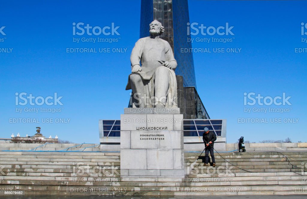 Worker clean with a pressure washer the monument to the founder of cosmonautics Konstantin Tsiolkovsky in Moscow. stock photo