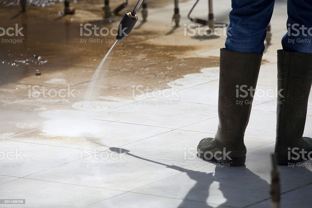 Worker Cleaning a Fountain by Pressure Washer stock photo