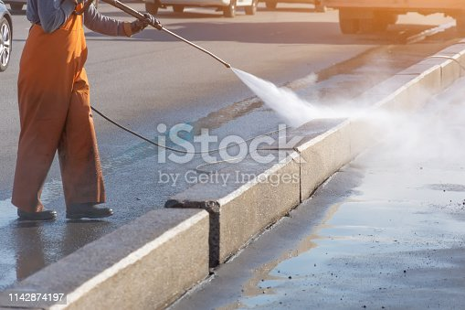 Worker cleaning driveway with gasoline high pressure washer splashing the dirt, asphalt road border. High pressure cleaning