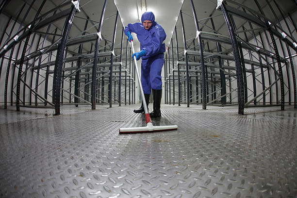 worker  cleaning floor in empty storehouse stock photo