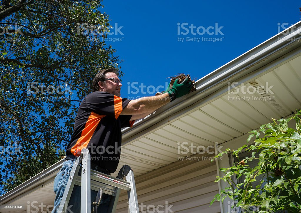 Worker Cleaning Gutters stock photo