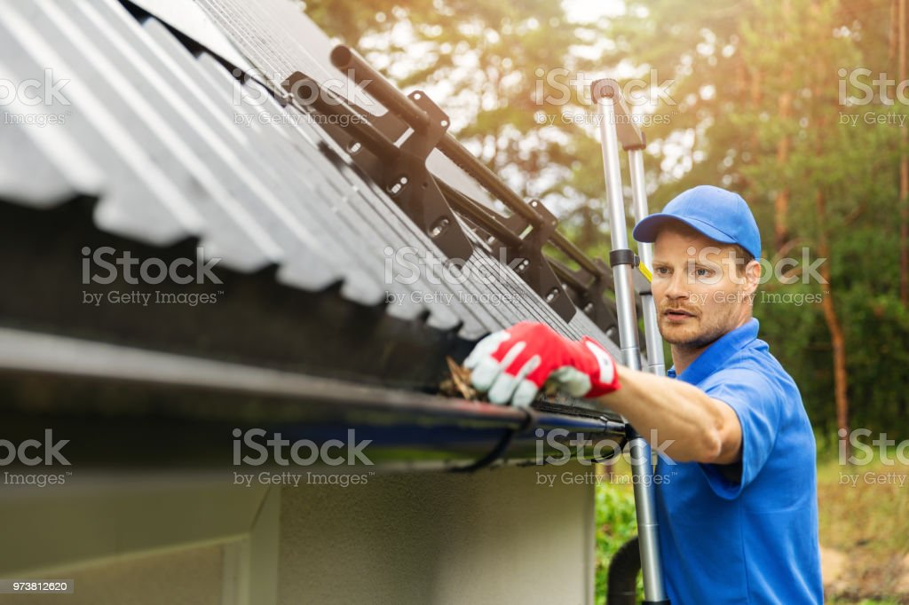 worker cleaning house gutter from leaves and dirt stock photo