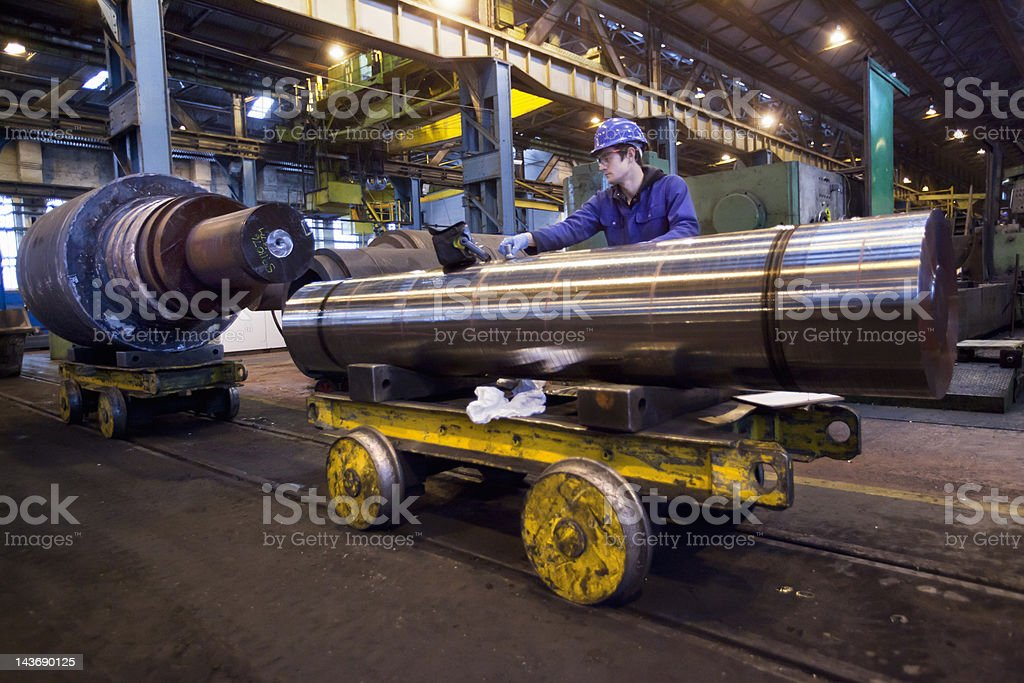 Worker cleaning metal in steel forge stock photo