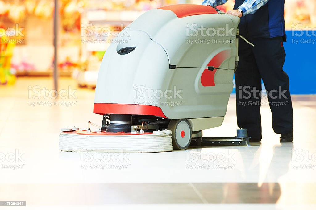 worker cleaning store floor with machine stock photo