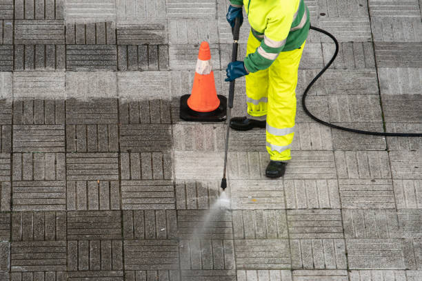 Worker cleaning the street sidewalk with high pressure water jet stock photo