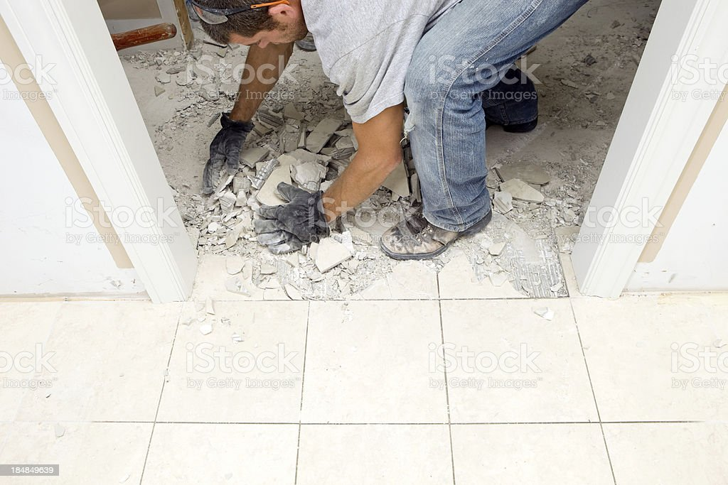 Worker Cleaning Up Tile Demolition stock photo
