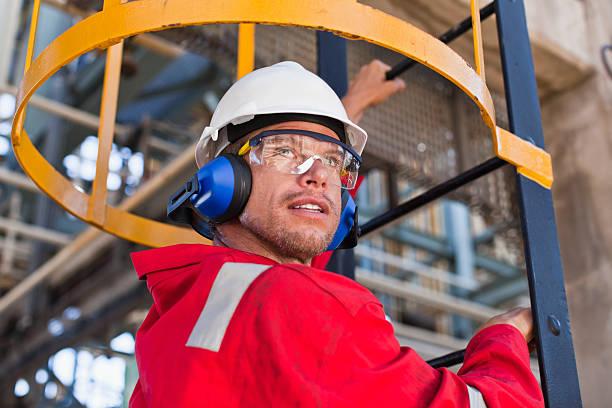 pracownik wspinaczka drabiny na rafineria naftowa - kask ochronny odzież ochronna zdjęcia i obrazy z banku zdjęć