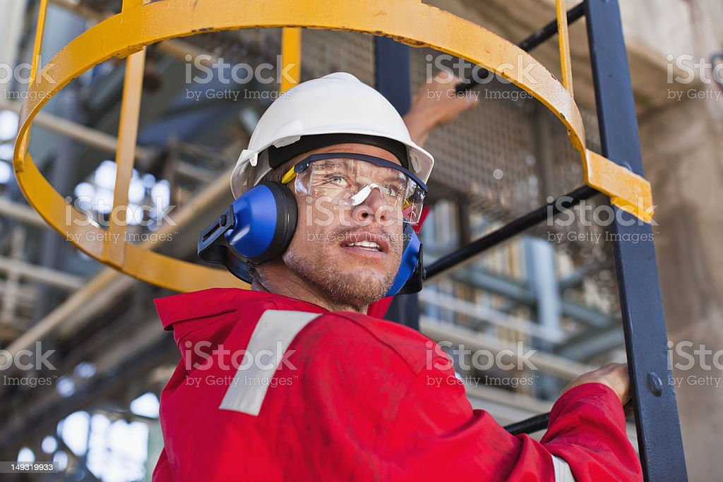 Worker climbing ladder at oil refinery stock photo