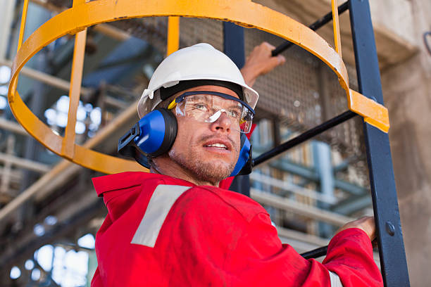 worker climbing ladder at oil refinery - refinery stock photos and pictures