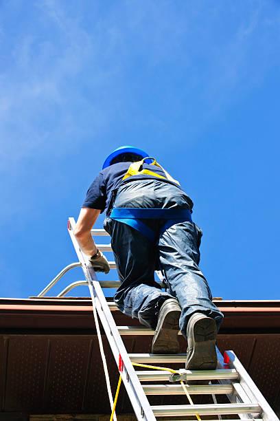 worker climbing ladder wearing safety harness and helmet - ladder stockfoto's en -beelden