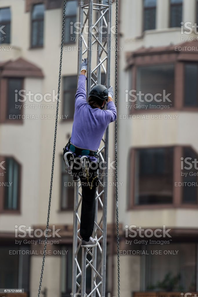 Worker climbs a scaffold through the city streets. royalty-free stock photo