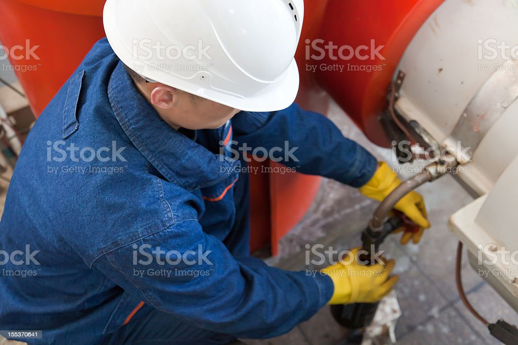 Worker collecting oil sample royalty-free stock photo