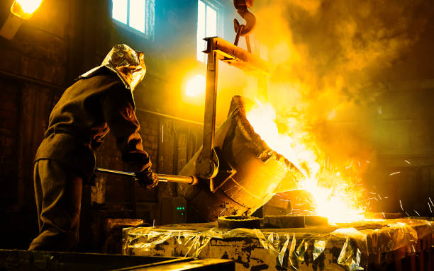 Worker controlling metal melting in furnaces. Workers operates at the metallurgical plant. The liquid metal is poured into molds. metal industry stock pictures, royalty-free photos & images