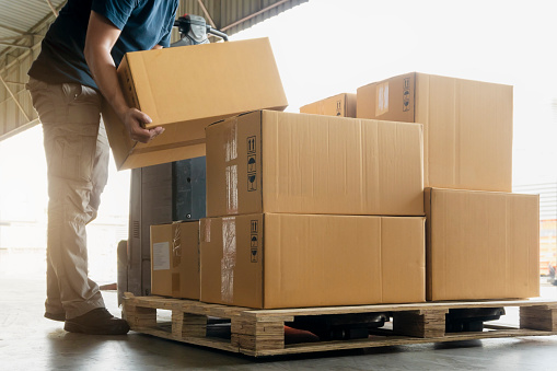 Worker courier lifting shipment boxes stacking on pallet, packaging. cardboard box, warehouse delivery service shipment goods, manufacturing warehouse.