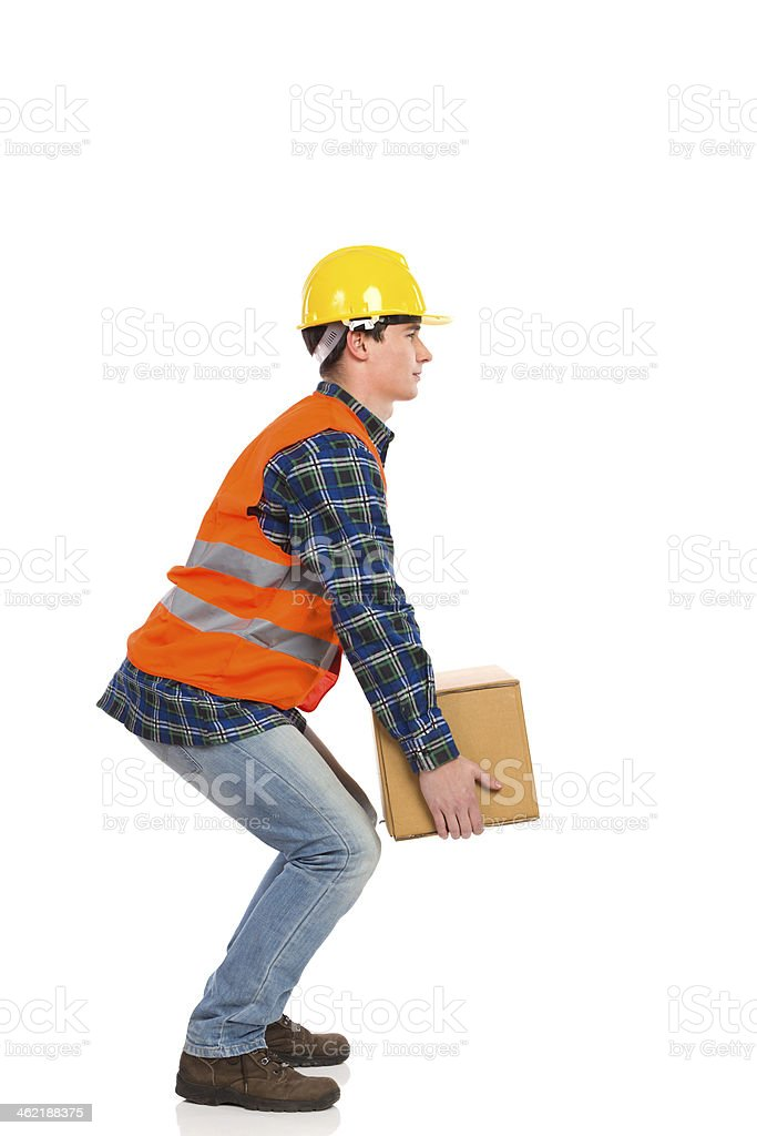 Worker crouching with a heavy package stock photo
