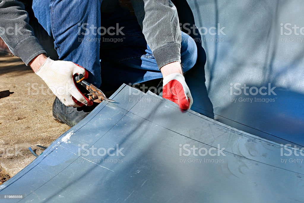 Worker cut stainless steel sheet shears of metal cutting stock photo
