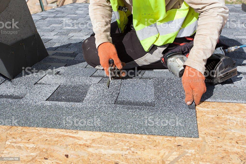 Worker cuts shingles witk scissors stock photo