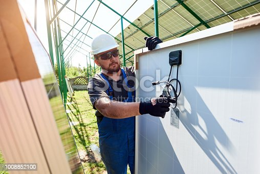 istock Worker cutting black pliers with special pliers, installing solar pannels. 1008852100