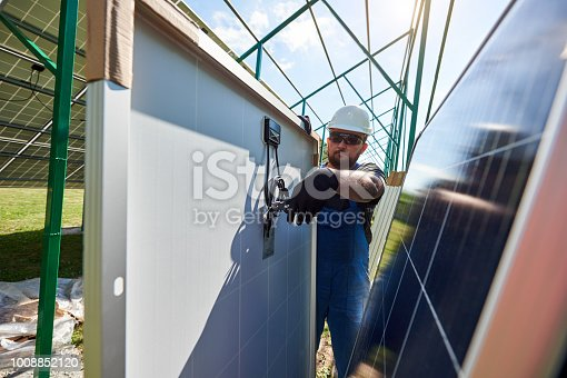 istock Worker cutting black pliers with special pliers, installing solar pannels. 1008852120