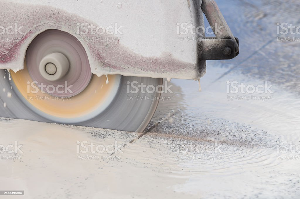 Worker cutting concrete road with diamond saw blade machine stock photo