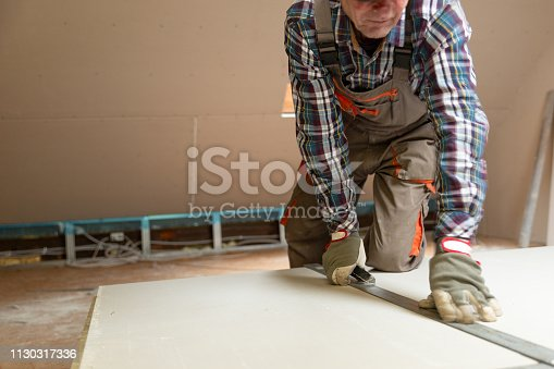 466705128 istock photo Worker cutting drywall plasterboard with construction knife. Attic renovation 1130317336