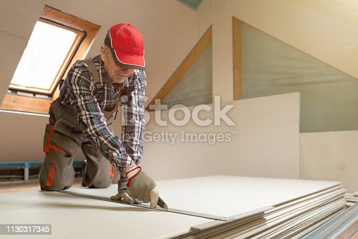 466705128 istock photo Worker cutting drywall plasterboard with construction knife. Attic renovation 1130317345
