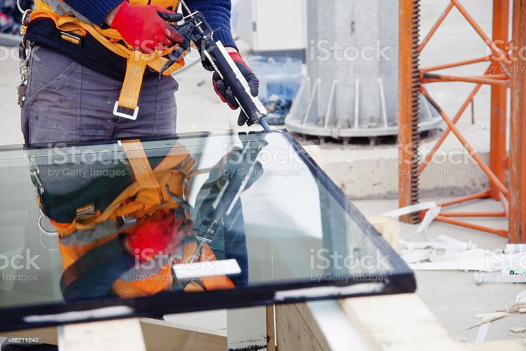 Worker cutting glass in a factory warehouse stock photo