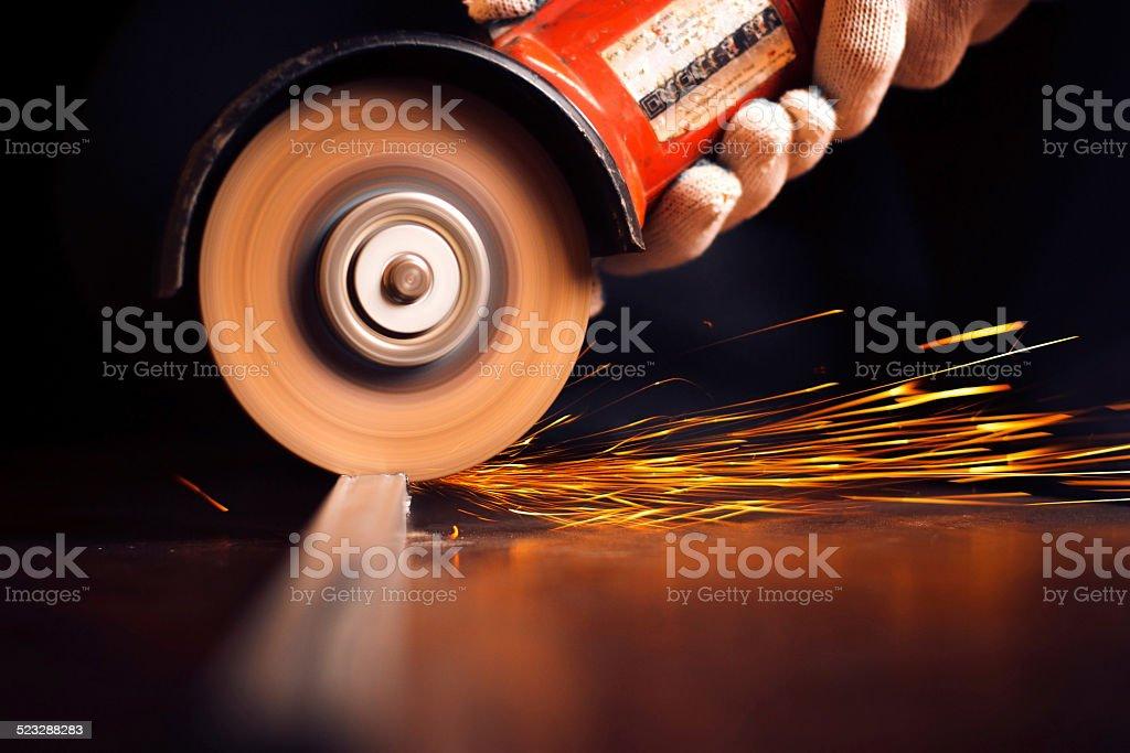 Worker cutting metal with grinder bildbanksfoto