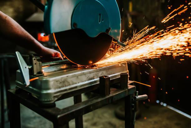 arbeitnehmer mit einer schleifmaschine schneiden metall. - europäisch geschliffene diamanten stock-fotos und bilder