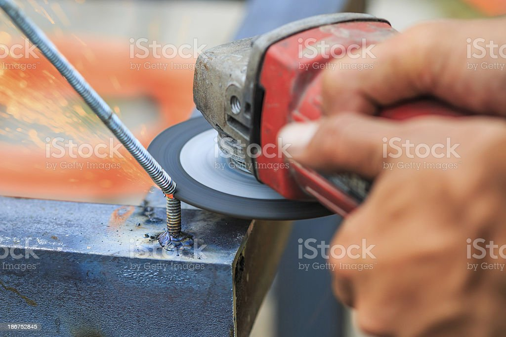 Worker cutting metal with grinder. Sparks while grinding iron stock photo