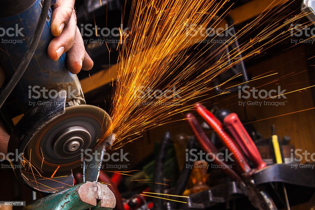 Worker cutting metal with grinder. Sparks while grinding iron. S stock photo