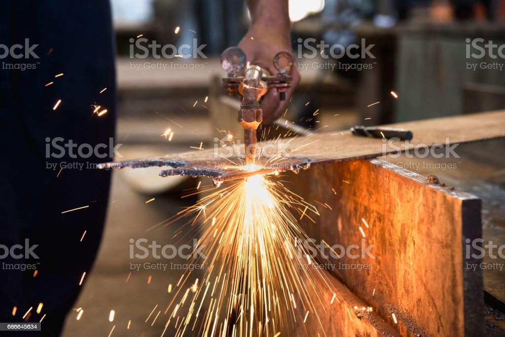 Worker cutting metalsheet by acetylene torch with bright sparks in fabication factory. Стоковые фото Стоковая фотография