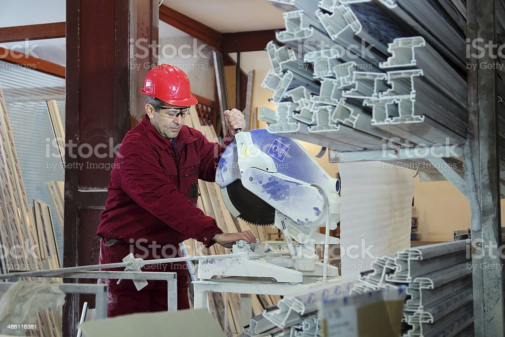 Worker Cutting PVC Profile with Circular Saw stock photo