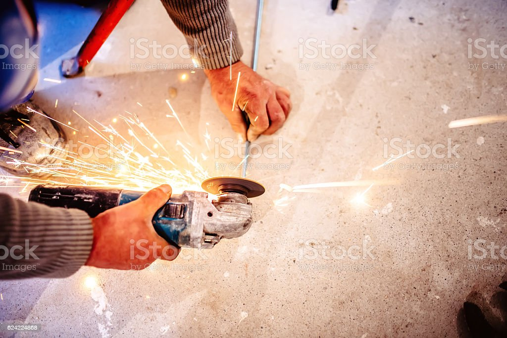 worker cutting steel bars using manual grinder stock photo