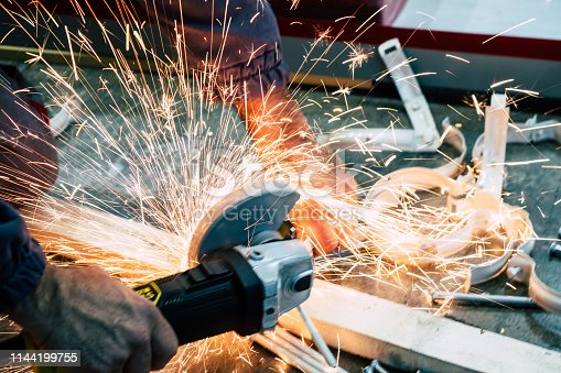 Worker using grinder to cut steel with sparks flying