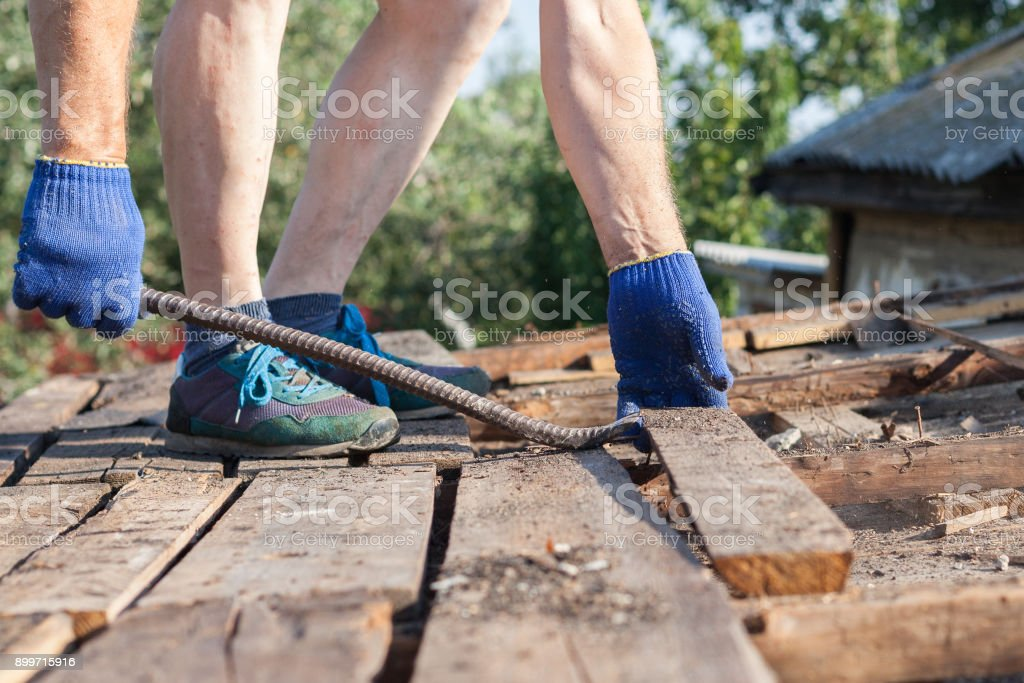 Worker demolishing old wooden boards from the roof  with crowbar tool stock photo